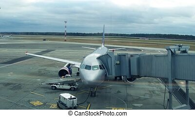 Modern silver airliner with attached jet bridge at the...