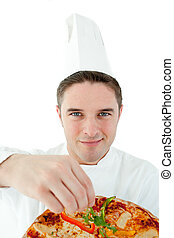 Sophisticated male cook holding a pizza against white...