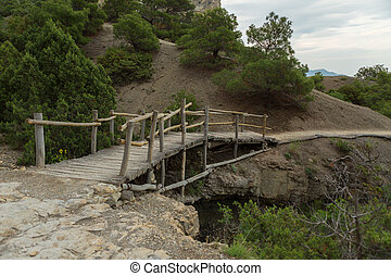 Wooden bridge on Trail Golitsyn - Falcon Path a mountain pathway carved at side of Koba-Kaya. Crimea