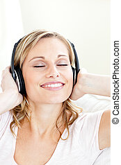 Radiant young woman listening to music wearing headphones in...