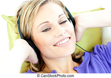 Joyful woman listening to music in the living-room at home
