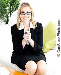 Charming businesswoman sending a text sitting on the sofa in...