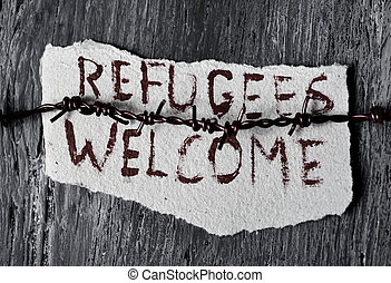 barbed wire and text refugees welcome - closeup of a barbed...