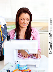 Bright caucasian woman using a sewing-machine in the kitchen...