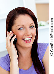 Laughing woman using her cellphone at home in the...