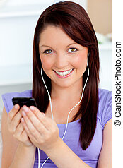 Happy woman using her cellphone to listen to music with...