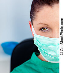serious female doctor with mask on her face looking at the...