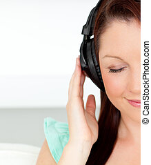 Delighted woman listening to music with headphones at home...