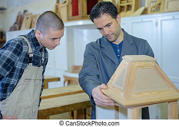 cabinetmaker teaching a young man his job