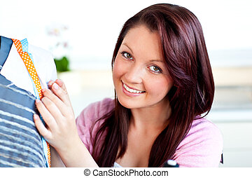 Smiling caucasian woman sewing in the kitchen at home