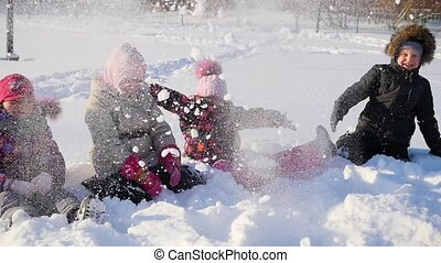 cheerful children playing in the snow throwing snow up in park