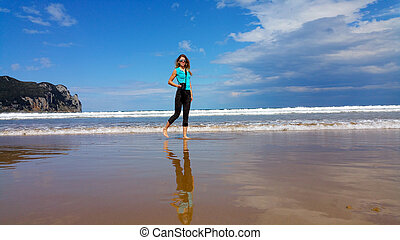 girl with camera walking on the water on the beach