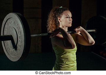 Young girl doing front squats.