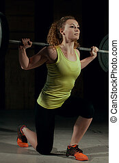 sporty woman exercising with barbell in gym