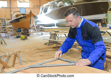 shipwright measuring the plywood