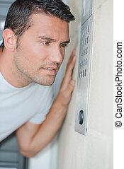 Man speaking into an intercom system