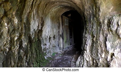 Walking into an old abandoned mine - Handheld shot of point...