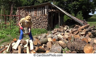 Worker prepare firewood for cold season. 4K - Villager man...
