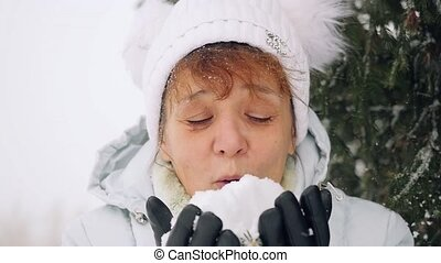 Mature happy woman in aged blowing snowflakes in slowmotion...