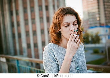 girl with a cigarette. young beautiful woman smokes a cigarette in the street