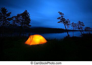 Camping - A tent lit up at dusk