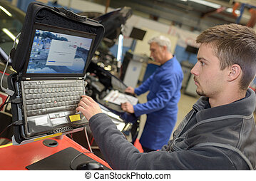 mechanic referring to a laptop for service order