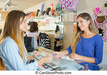 Lady in clothes shop, paying by card