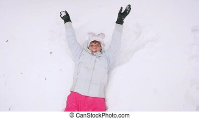 Happy mature woman in winter wear lying in snowdrift...