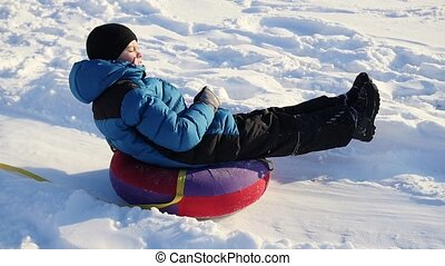 a happy child rides in snowtube on a snowy hill