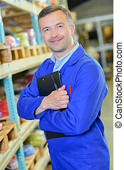 Man in warehouse holding clipboard to his chest