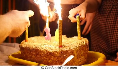 birthday cake with candles spark fireworks in dark room. ignition candles