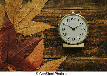 Old alarm clock between yellow leaves