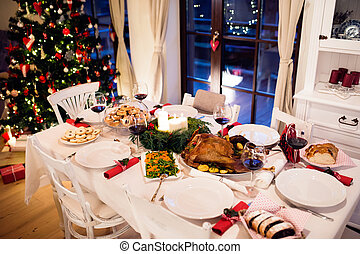 Christmas meal laid on table in decorated dining room....