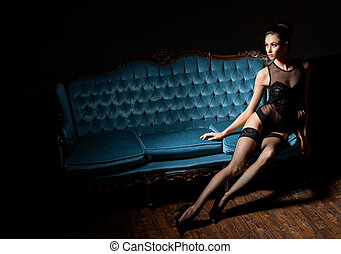 Sexy woman in lingerie sitting on a vintage sofa - Sexy and...