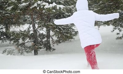 Attractive young woman running in snowdrift shaking snowy branches enjoying the winter in slowmotion during snowfall.