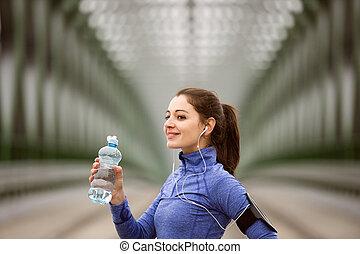 Young runner resting, drinking water on green steel bridge -...