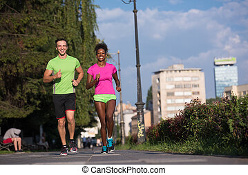 young smiling multiethnic couple jogging in the city -...