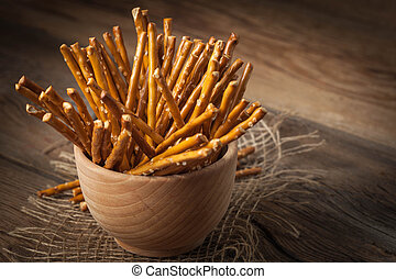 Salty pretzel sticks. - Salty pretzel sticks on a dark...