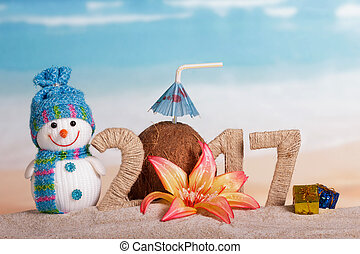 Christmas snowman, coconut and inscription 2017 in the sand,...