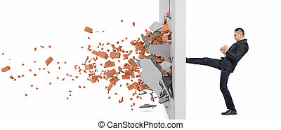Businessman kicking hard the wall and crush it, side view....
