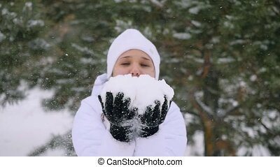 Young woman blowing snowflakes during snowfall enjoying winter time in slowmotion.