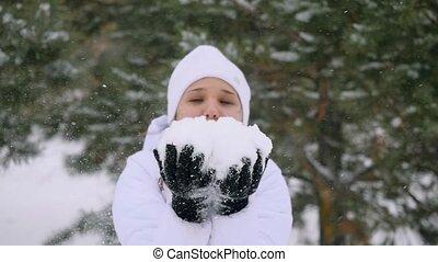 Young woman blowing snowflakes during snowfall enjoying...