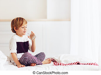 young kid, boy starts his morning with a glass of fresh...