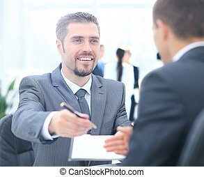 Businessman giving a pen to seal  deal with his partner