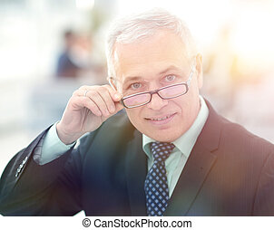 Portrait of mature businessman with colleagues interacting...