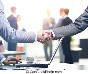 Confident business handshake. Close-up view of a handshake. business office in formal wear and work at a laptop