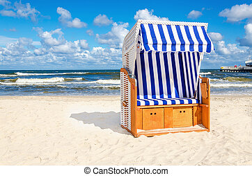 Blue and white wicker chair on sandy beach with cloud