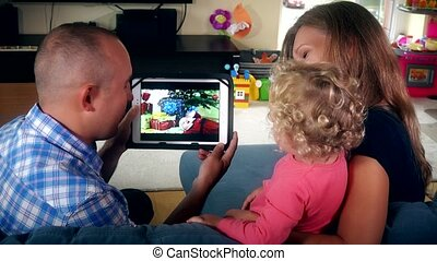 Lovely family child father and mother watch family video movie on tablet