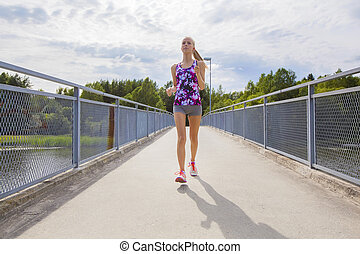 Focused young woman running on bridge over a lake -...