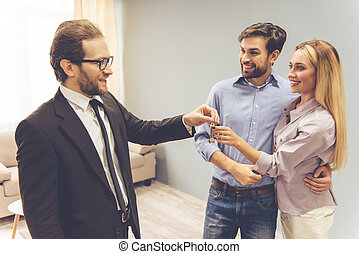 Couple and a realtor - Handsome realtor in suit is giving...